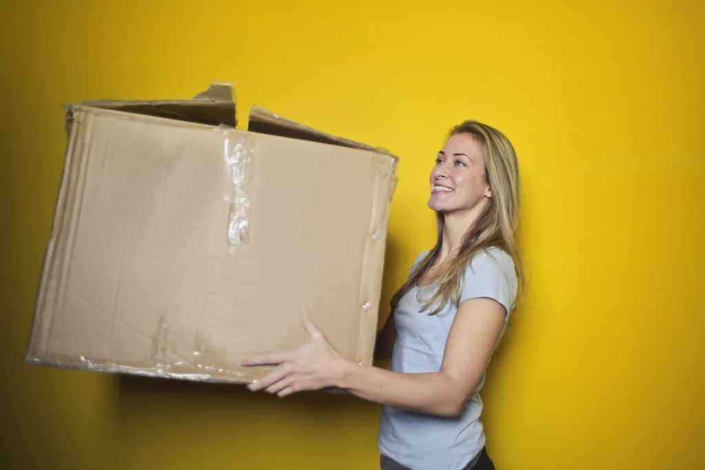 Une femme portant un carton de déménagement