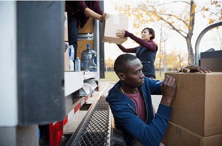 personnes mettant des cartons dans un camion pendant un déménagement