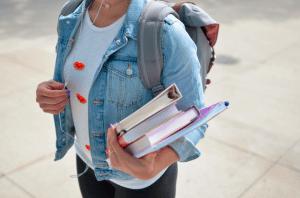 Etudiante porte des livres de cours dans les bras